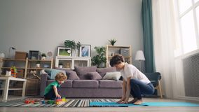 Madre hermosa que hace yoga en casa y que mira a su hijo el jugar con los juguetes almacen de video