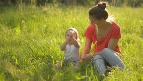 Madre hermosa que juega con su pequeña hija en el parque, diente de león del soplo