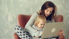 Madre hermosa que usa el ordenador portátil con el pequeño bebé en sus rodillas almacen de metraje de vídeo