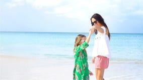 Madre hermosa y pequeña hija en la playa del Caribe que juega junto Cámara lenta almacen de video
