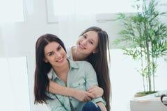 Madre hermosa y su hija linda que sonríen y que presentan en casa Imágenes de archivo libres de regalías