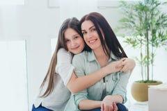 Madre hermosa y su hija linda que sonríen y que presentan en casa Fotos de archivo