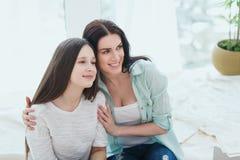 Madre hermosa y su hija linda que sonríen y que presentan en casa Imagen de archivo libre de regalías