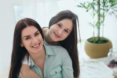 Madre hermosa y su hija linda que sonríen y que presentan en casa Fotografía de archivo