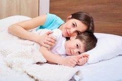 Madre hermosa y su hijo abrazados en cama Fotos de archivo