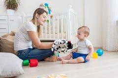 Madre hermosa y sus 10 meses del hijo del bebé que juega con el perrito Fotos de archivo