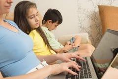 Madre, hija, hijo con el ordenador portátil y PC de la tableta Apego del Internet Fotos de archivo