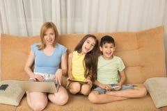Madre, hija, hijo con el ordenador portátil y PC de la tableta Apego del Internet Imagen de archivo