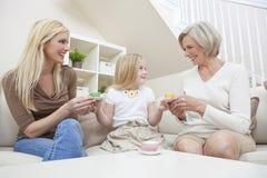 Madre, hija, té de consumición de la familia de la abuela Imágenes de archivo libres de regalías