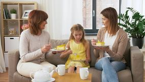 Madre, hija y abuela comiendo la torta almacen de metraje de vídeo