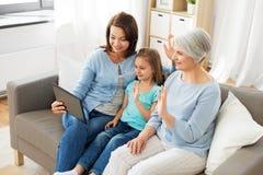 Madre, hija y abuela con PC de la tableta imagen de archivo libre de regalías