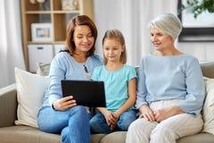 Madre, hija y abuela con PC de la tableta foto de archivo
