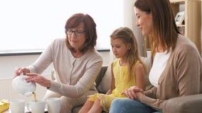 Madre, hija y abuela teniendo la fiesta del té metrajes