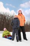 Madre, hijo e hija colocándose en nieve Imagen de archivo libre de regalías