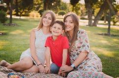 Madre, hijo e hija felices en el parque Familia que se divierte al aire libre Concepto de familia feliz Fotografía de archivo