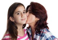 Madre hispánica que besa a su hija hermosa Imagen de archivo