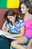 Madre hispánica y su lectura bonita de la hija Imagenes de archivo