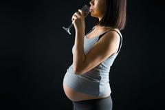 Madre incinta bevente sulla a sopra backgroun leggero scuro drammatico Fotografia Stock