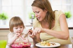 Madre incinta in cucina che mangia pollo e vege Immagine Stock