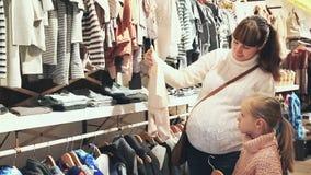 Madre incinta e una bambina che sceglie i vestiti stock footage