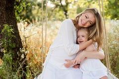 Madre incinta felice con la figlia che sorride un giorno di estate Immagini Stock