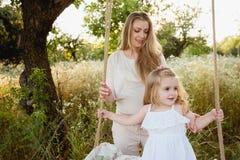 Madre incinta felice con la figlia che sorride un giorno di estate Immagine Stock Libera da Diritti