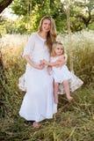 Madre incinta felice con la figlia che sorride un giorno di estate Immagini Stock Libere da Diritti