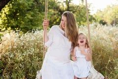 Madre incinta felice con la figlia che sorride un giorno di estate Fotografie Stock
