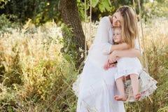 Madre incinta felice con la figlia che sorride un giorno di estate Immagine Stock