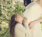 Madre incinta felice e la sua piccola figlia Fotografie Stock