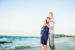 Madre incinta, padre e figlia della famiglia felice abbracciantesi e guardanti avanti al mare durante la passeggiata sulla spiagg fotografie stock libere da diritti