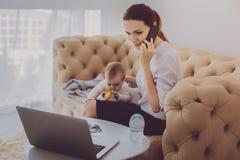 Madre independiente que habla en el teléfono mientras que calma a su niño dormido imagen de archivo