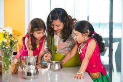 Madre india que cocina con sus hijas foto de archivo