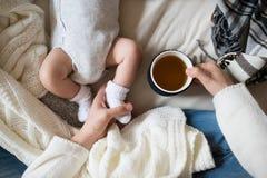 Madre irriconoscibile con il figlio del neonato che si trova sul letto immagine stock libera da diritti