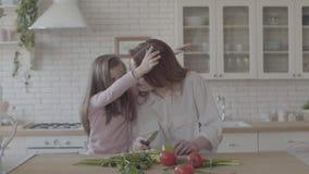 Madre joven adorable del retrato y su pequeña hija linda en la cocina grande, cocinar de la mujer y la pequeña muchacha de besarl almacen de video