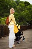 Madre joven alegre que da un paseo con recién nacido en carro Imagen de archivo libre de regalías