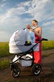 Madre joven alegre que saca a su bebé del cochecito de niño Fotografía de archivo