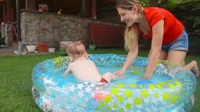 Madre joven alegre que salpica el agua con su bebé de 1 año en la piscina inflable metrajes