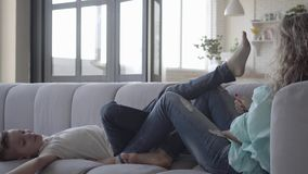Madre joven bonita que sienta en el sofá con ella al pequeño hijo de mentira El muchacho que juega con la mujer con sus piernas,  almacen de metraje de vídeo