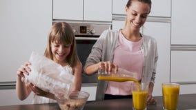 Madre joven bonita y su hija que preparan el desayuno en la cocina en casa almacen de video