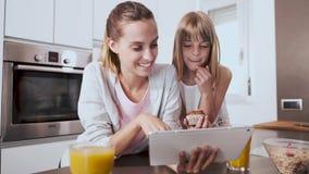 Madre joven bonita y su hija que usa la tableta digital mientras que desayunando en la cocina en casa almacen de video