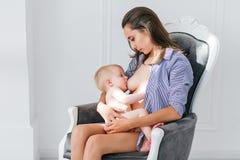 Madre joven brestfeeding su niño recién nacido que se sienta en butaca del vintage Paredes blancas en fondo Bebé del oficio de en fotos de archivo