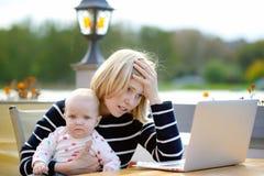 Madre joven cansada que trabaja oh su ordenador portátil fotografía de archivo libre de regalías