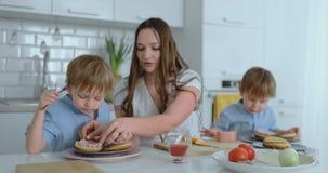 Madre joven con dos hijos jovenes en la cocina en la tabla que prepara la hamburguesa para el almuerzo almacen de metraje de vídeo