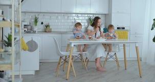Madre joven con dos hijos jovenes en la cocina en la tabla que prepara la hamburguesa para el almuerzo metrajes