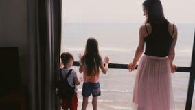 Madre joven con dos niños emocionados felices junto en la cámara lenta de observación de la opinión del mar de la ventana grande  almacen de metraje de vídeo