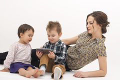 Madre joven con dos niños que miran historietas en el teléfono celular Fotografía de archivo libre de regalías