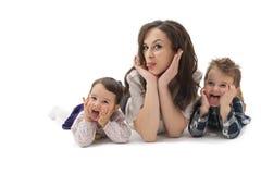 Madre joven con dos niños que se divierten en un blanco Foto de archivo libre de regalías