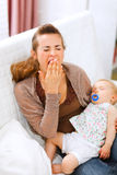 Madre joven con el bebé durmiente en la desviación de las manos Foto de archivo libre de regalías