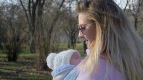 Madre joven con el bebé en honda que pasa tiempo en parque en el ocio metrajes